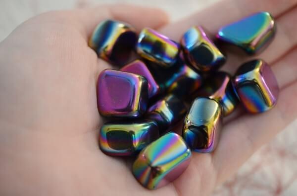 A woman holding many Rainbow Hematite stones